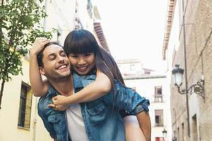 gelukkig liefdevol paar. gelukkige jonge man meeliften zijn vriendin foto