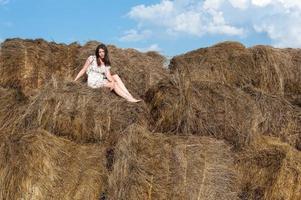 jonge mooie vrouw ontspant op hooi foto