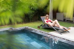 vrouw ontspannen op chaise longue bij zwembad.