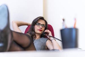 ontspannen zakenvrouw praten over de telefoon en het gebruik van haar laptop foto