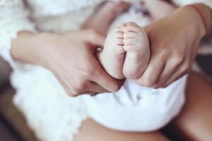 foto van schattige baby voeten in handen van de moeder