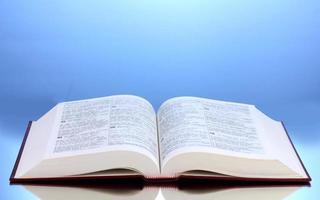 open boek over reflecterend oppervlak van tabel op blauwe achtergrond