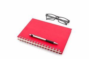 rood dagboekboek met oude glazen en pen.