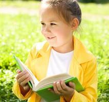 het meisje leest in openlucht een boek foto
