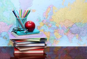 terug naar school. een appel, kleurpotloden, glazen en boeken foto