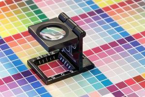 close-up van een loep op een kleurrijke testafdruk foto
