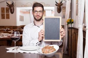 lachende jonge man met schoolbord menu foto