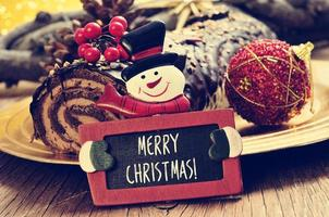 yule log cake en schoolbord met tekst vrolijk kerstfeest foto