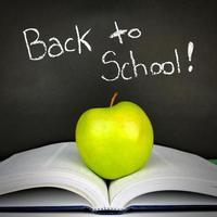 terug naar schoolbord met boek en appel foto