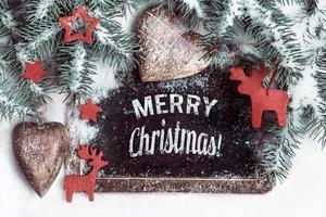 """zwart bord op sneeuw met de tekst """"Merry Christmas!"""" foto"""