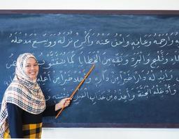 hand van de leraar lesgeven in Arabische letters op schoolbord, foto