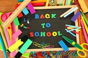 klein bord met schoolbenodigdheden op witte achtergrond