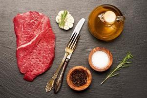 rauwe biefstuk en specerijen op het schoolbord foto
