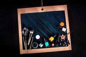 verschillende cosmetica en make-up op schoolbord of schoolbord foto