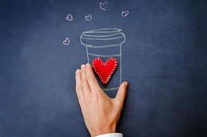 mannen hand houden glas koffie op een schoolbord foto
