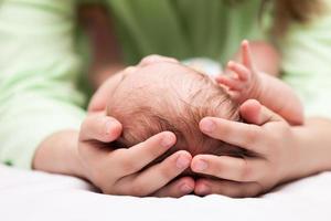 schattig slapende pasgeboren baby kind op handen van de moeder