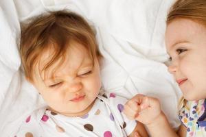 domme baby in lakens met grote zus foto