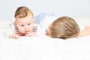 kleine jongen pasgeboren zusje met de hand te houden foto