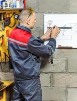 mechanische werknemer die zijn instructies bestudeert foto