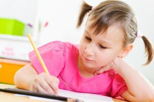 schattig klein meisje studeren thuis foto