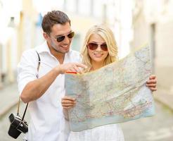 lachende toeristen die kaart van de stad bestuderen
