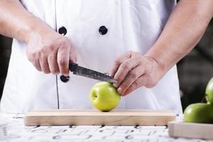 handen van de chef-kok die groene appel snijden foto
