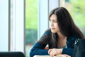 jonge student kijkt uit raam tijdens het studeren foto