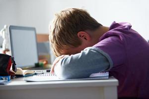 een vermoeide jongen die in zijn kamer studeert foto