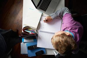 bovenaanzicht van jongen studeren in slaapkamer foto