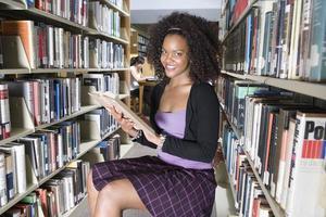 vrouwelijke universitaire student studeert in de bibliotheek, portret foto