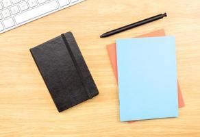 leeg zwart, blauw en oranje notebook, pen op tafel foto