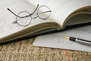 boek met hiërogliefen, papyrus, vertaling, bril en pen foto