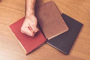man hand die op sommige boeken op een lijst raakt foto