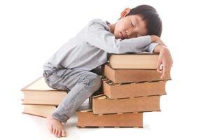 Aziatische schattige jongen zitten en slapen op stapel boeken. foto