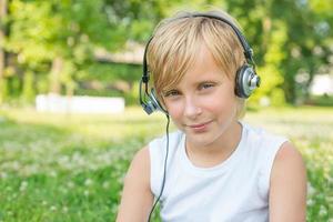 jongen met koptelefoon buitenshuis foto