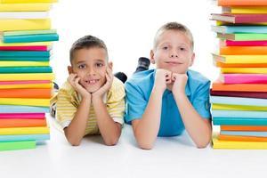 studenten zitten achter stapel boeken op witte achtergrond foto