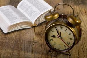 bijbel met klok op hout foto