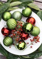 Kerst ornamenten en bessen op een bord foto