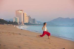 sport vrouw doen oefening op het strand van de stad. foto