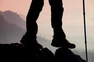 vrouw wandelaar benen in toeristische laarzen staan op berg rots foto