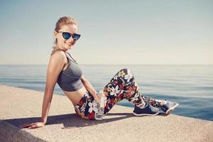 jonge fitness blonde vrouw houdt fles water na pasvorm foto