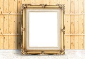 leeg gouden vintage frame op marmeren vloer en houten plank foto