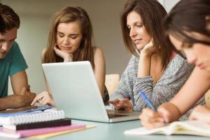 lachende vrienden zitten studeren en met behulp van laptop foto