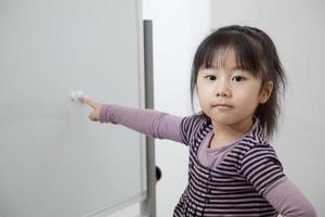 het meisje dat leert op een wit bord foto