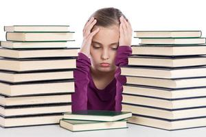 schattig meisje geconcentreerd met veel boeken foto