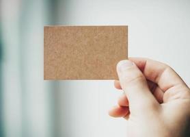 mannelijke hand met ambachtelijke visitekaartje op de onscherpe achtergrond foto