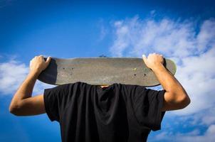 jongen omarmt zijn skateboard - lifestyle concept foto