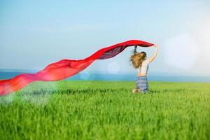 jonge gelukkige vrouw in een tarweveld met stof. zomer levensstijl foto