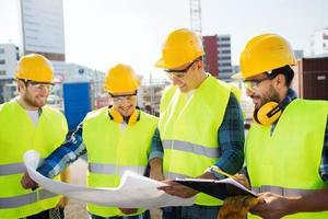 groep bouwers met tablet pc en blauwdruk foto