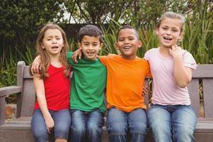 gelukkige kinderen zitten samen op een bankje foto